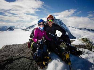 Couple on rock near summit of Mt Aspiring, NZ