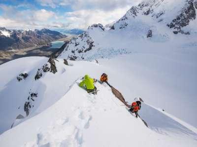 People on peak looking at NZ alpine view